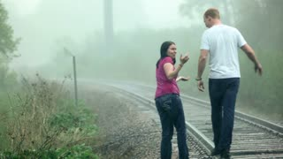 Heavy Rain on Couple on Train Tracks