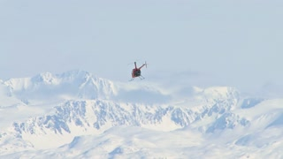 Helicopter Flying Away To Snowy Mountains