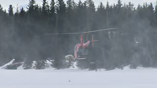 Helicopter Hovering Over Snow