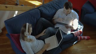 High angle shot of a young people at home. They lying on the sofa and working with tablet computer and laptop. Girl showing monitor to man, he approving it and giving her a high-five