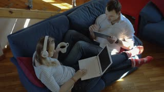 High angle shot of young couple lying on the sofa at home. Woman in headphones using laptop and having tea while excited man working with tablet computer
