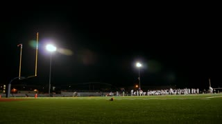 High school football team practicing in a stadium at night.