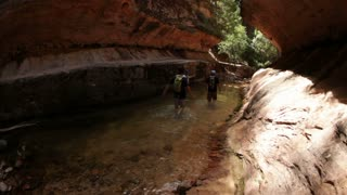 Hikers Wading Through Gorge Sream