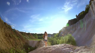 Hiking woman in mountains. Strong happy woman tourist is reaching the point of her journey and standing with hands up in sunny canyon. Slow motion filmed at 240 fps.