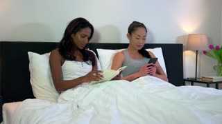 Homosexual couple, gay people, two lesbians, same sex marriage relationship between Asian girls. Woman reading book, partner with smartphone taking selfie in bed at home. Multiethnic lovers in bedroom