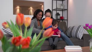 Homosexual couple, gay people, young lesbian women, same sex marriage relationship between Asian girls. Mother using ipad digital tablet with child and partner, mom with woman and baby