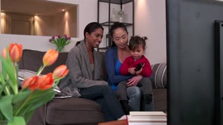 Homosexual couple, gay people, young lesbian women, same sex marriage relationship between Asian girls. Multi-ethnic family watching TV with adopted child, mixed race lesbians having fun with baby