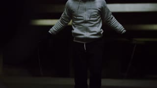 Hooded athlete skipping intensely at night with a jump rope
