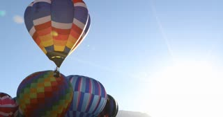 Hot air balloon rises with bright sun flare in the background