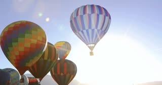 Hot Air Balloons float through sun burst