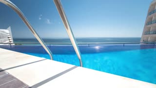 Hotel swimming pool with sunny reflections and blue water timelapse, view on the beach of Sesimbra, Portugal 4K