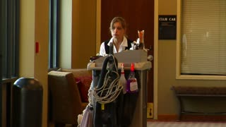 Housekeeper In The Hotel Pushes Cart
