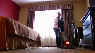 Housekeeper Vacuums Hotel Room
