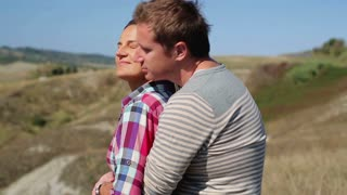 Hugging couple enjoying panoramic view of Tuscany, crane shot