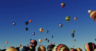 Hundreds of colorful hot air balloons floating in the sky