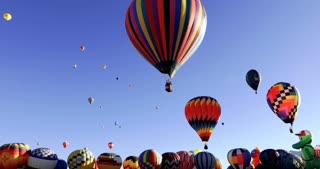Hundreds of vibrant colorful hot air balloons lift off into the sky