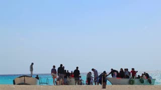 HURGHADA, EGYPT - FEBRUARY 1, 2014: Group of tourists arriving on Paradise Island by boats