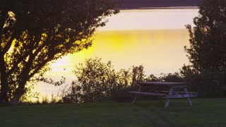 Idyllic Picnic Table Next To Lake at Sunset