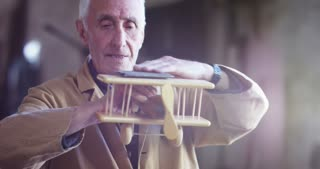 in an old carpentry an elder is working the wood to create a toy airplane with traditional instruments