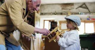 in an old carpentry shop a child and grandfather playing with a wooden airplane concept of tradition that continues over time