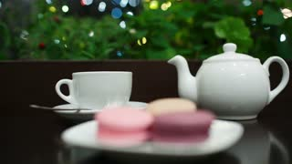 In cafe: pouring tea into white cup, then focus on hand taking tasty macaroons. Twinkling lights in greenery in background.