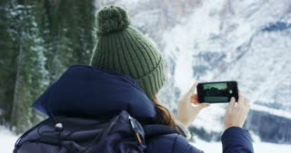 in mountains on vacation A girl uses a mobile phone or smartphone for texting,calling, take pictures, make selfies and video calls friends and family from home. Concept:holiday,technology,love,message