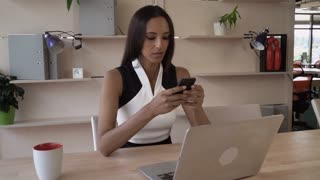 Indian businesswoman texting message on the mobile phone. Multicultural woman writing sms on the phone. Female in the office write mail on the telephone. Young girl with shine black hair communicate