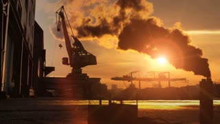 industrial background. smog pollution smoke. cranes. sunset sun flare