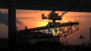 industrial cranes business. logistics. silhouette. time lapse. sunset. smog