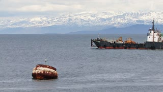 Industrial Vessel Passing Buoy And Mountains