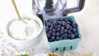 Ingredients to make smoothie with plain yogurt and fresh berries on the table.