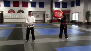 Instructor Kicking Bag Held by Woman in Karate Studio 2