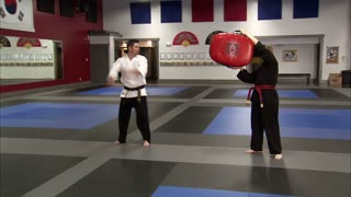 Instructor Kicking Bag Held by Woman in Karate Studio
