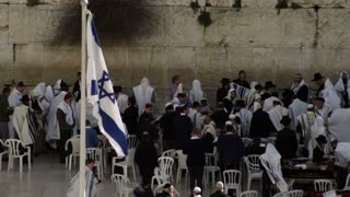 Israeli Flag Blowing In Wind Near Worshippers
