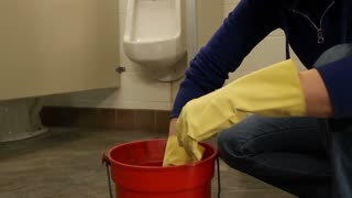Janitor Squeezing Out Rag In Men's Bathroom