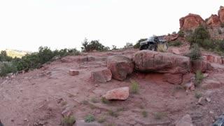 Jeep Rolling Over Redrock Landscape