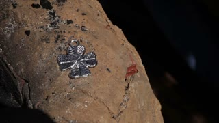 Jewellery cross adorning on a stone. Clip 3.