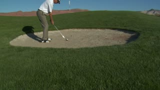 Jib  Shot Of Man Hitting A Golf Ball From Sand Trap