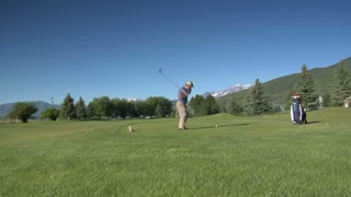 Jib Shot Of Man Teeing Off On Golf Course With Snowy Mountains Indistance