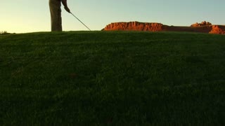 Jib Shot Of Man Teeing Off On Golf Course With Sunset And Red Rock Cliffs