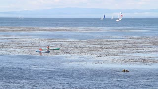 Kayakers Glide Through Kep, Sailboats Behind