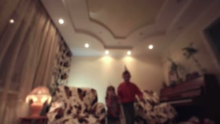 Kids coming to camera and making noise through party horn on blurred room background