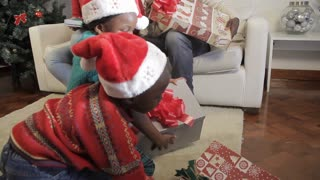 Kids giving their mother her christmas presents