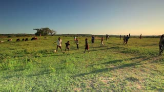 Kids Playing Soccer in a Field in Africa