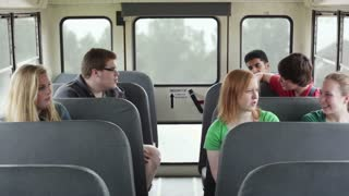 Kids Sit and Talk in Back of Bus