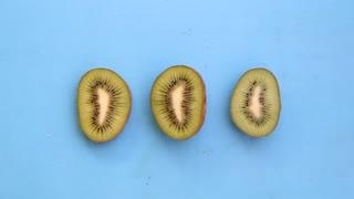 Kiwi fruit on blue background, tasty vegetarian dishes