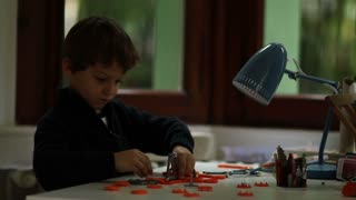Lamp Turns On While Young Boy Plays With Toys And Figuring Out Puzzle