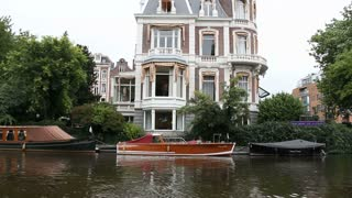 Large Home And Wooden Boat On Amsterdam Canal