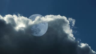 Large moon in day sky behind clouds