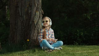 Laughing girl listening to music. Child sitting under a tree. In her hands the phone. Child is online. Zooming